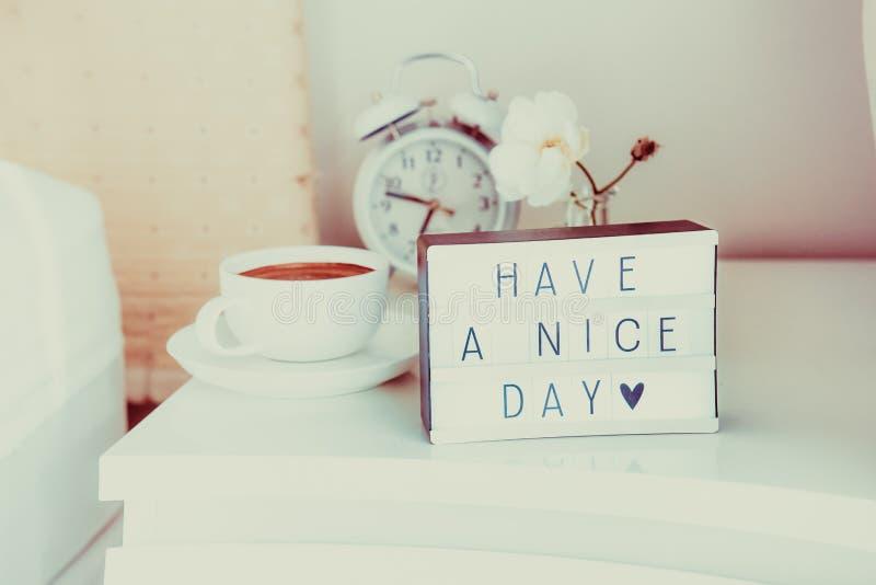 Heb een aardig dagbericht op aangestoken vakje, wekker, kop van koffie en bloem op de bedlijst in zonlicht Goedemorgenstemming royalty-vrije stock afbeelding