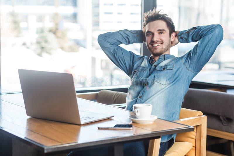 Heb een onderbreking! Het portret van knappe succesvolle gebaarde jonge freelancer in jeansoverhemd zit in koffie en heeft een ru stock afbeelding