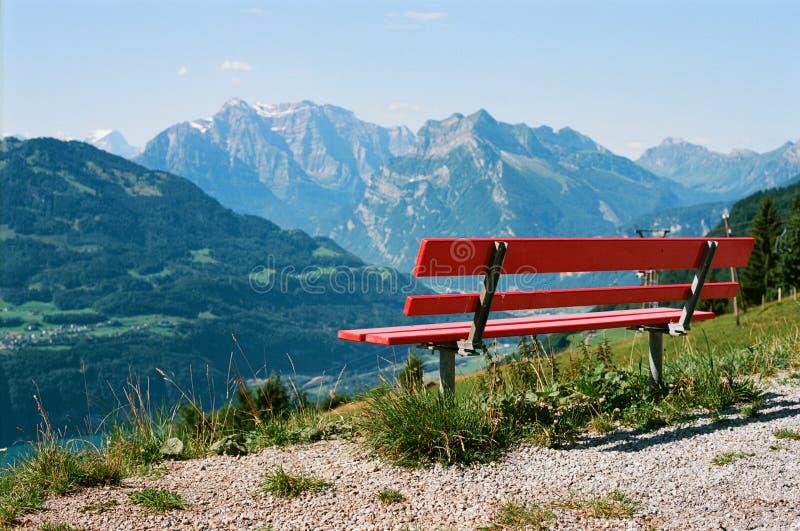 Heb een rust in de Zwitserse alpen met een mooie mening over een houten rode bank royalty-vrije stock fotografie