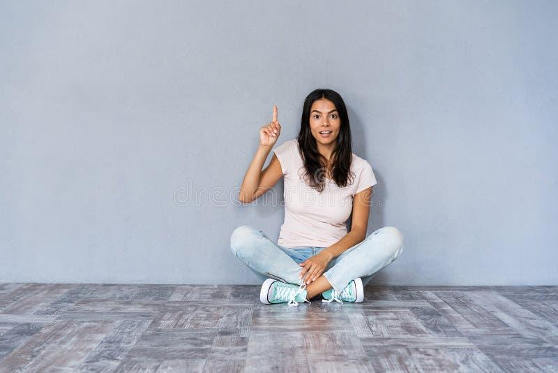 Heb idee! Leuke vrouw die in die vrijetijdskleding met benen zitten op de vloer gesturing wijsvinger die omhoog worden gekruist,  royalty-vrije stock foto's