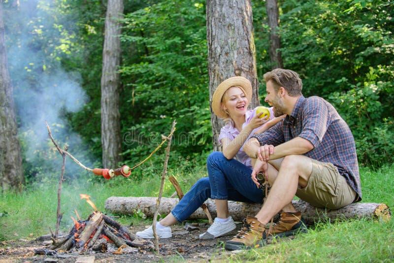 Heb snack Paar het ontspannen zit op logboek die snacks hebben De familie geniet van romantisch weekend in aard De meisjesaanbied royalty-vrije stock afbeeldingen