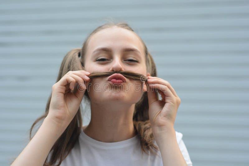 Hebbend de leeftijdsmeisje van de prettiener - het glimlachen en makend snor met bundel van haar Openlucht dicht omhooggaand port stock foto