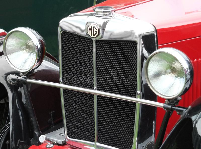 Chrome front grill headlamps and bumper of a Red Mg TC vintage sports car royalty free stock photos