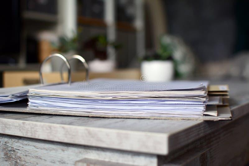 Hebelbogendatei mit vielen Seiten von den Dokumenten, die auf Tabelle mit undeutlichem Hintergrund liegen stockfotografie