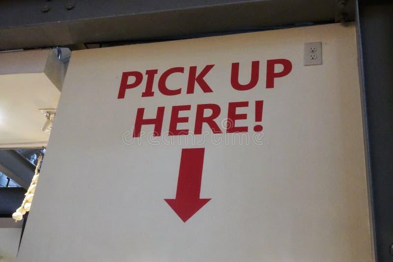Heben Sie hier Zeichen an einem Restaurant auf stockfotos