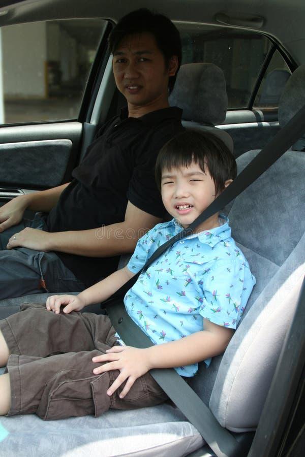 Hebilla del muchacho y del hombre encima del cinturón de seguridad fotografía de archivo