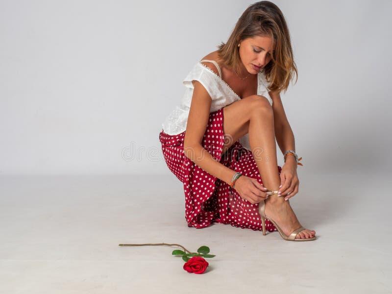 Hebilla rubia de la mujer sus zapatos en el fondo blanco foto de archivo