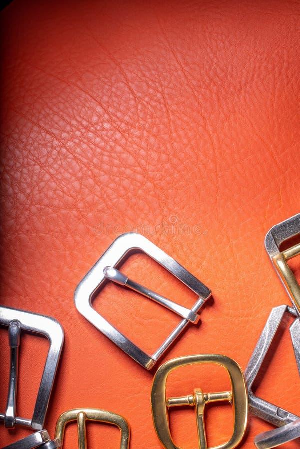 Hebillas del cinturón en fondo rojo de la plena flor Materiales, accesorios en el escritorio del trabajo de los craftman de cuero imagenes de archivo