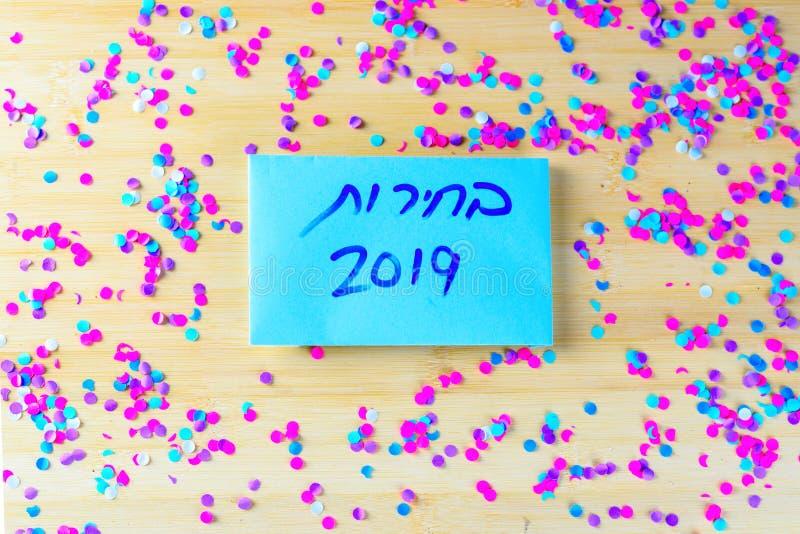 Hebreeuwse tekstverkiezingen 2019 bij het stemmen van over document over houten raad met confettienachtergrond royalty-vrije stock foto's