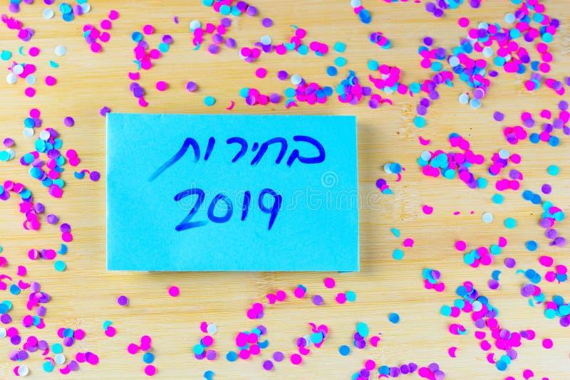 Hebreeuwse tekstverkiezingen 2019 bij het stemmen van over document over houten raad met confettienachtergrond stock afbeeldingen