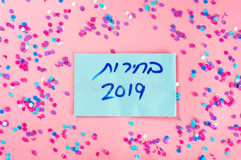 Hebrew text :Elections 2019 on voting paper over pink with colorful confetti background. Hebrew text Elections 2019 on voting paper over pink with colorful royalty free stock photos