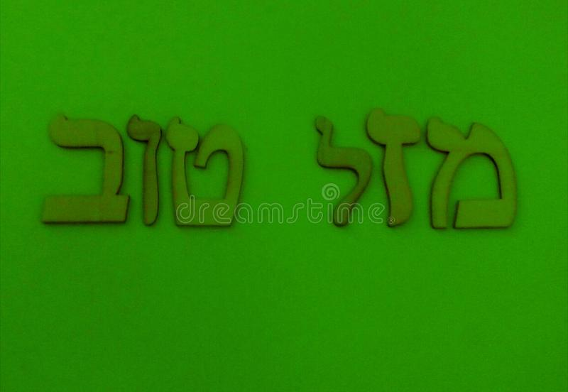 """Hebrew words. In Hebrew""""Mazal Tov"""",in English""""Good Luck""""on green backround royalty free illustration"""