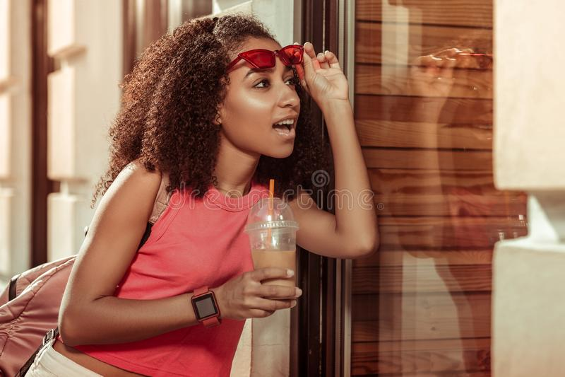 Hechizando a la mujer afroamericana encantadora del joven-adulto que mira asombrosamente la ventana foto de archivo libre de regalías