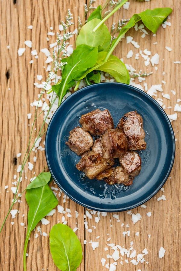 Hecho Fried Diced Marinated Beef en la placa de cerámica azul en el panel de madera con la sal y la verdura del mar adornadas imagen de archivo