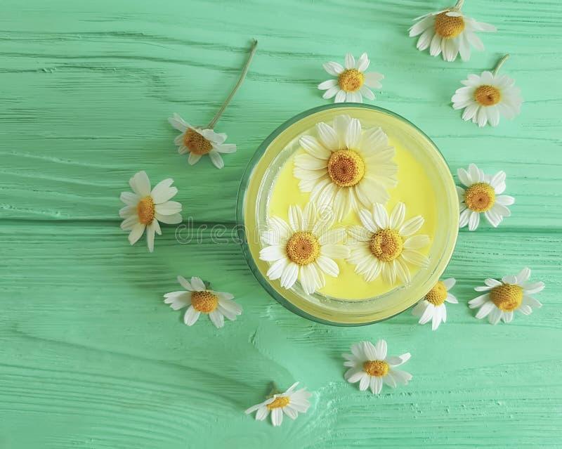 Hecho a mano de cristal cosmético poner crema, protección del producto del ungüento de la flor de la margarita del extracto en el fotos de archivo libres de regalías