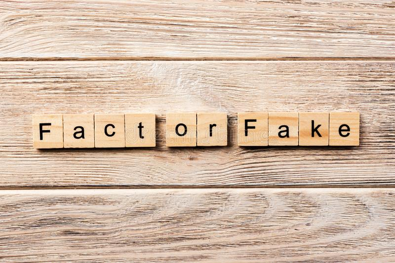 Hecho o palabra de la falsificación escrita en el bloque de madera hecho o texto en la tabla, concepto de la falsificación imagenes de archivo