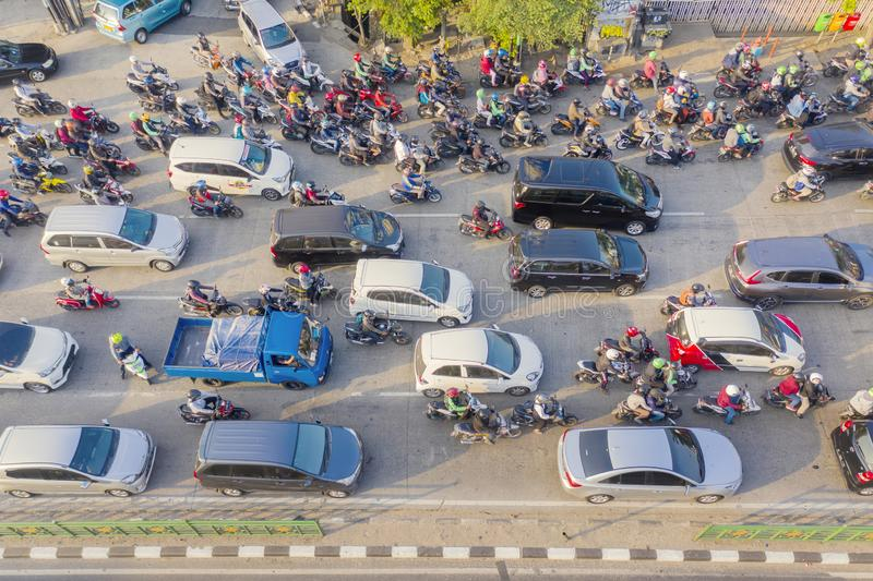 Hectic traffic with crowded cars and motorcycles. JAKARTA - Indonesia. August 08, 2019: Aerial view of hectic traffic with crowded cars and motorcycles on the royalty free stock photos