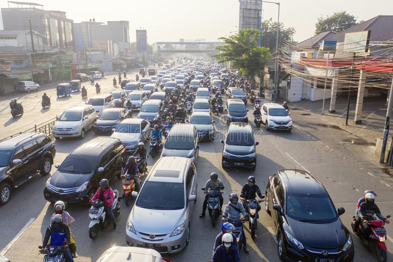 Hectic traffic with crowded vehicles on the road. JAKARTA - Indonesia. August 08, 2019: Drone view of hectic traffic with crowded cars and motorcycles on the stock photography