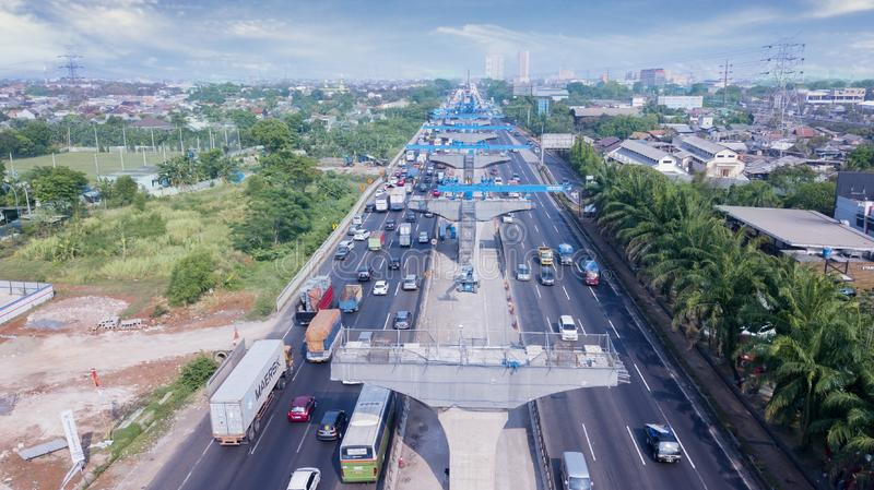 Hectic traffic on highway near elevated toll pilings. West Java, Indonesia - October 10, 2018: Aerial view of hectic traffic on the highway near pilings of stock photos