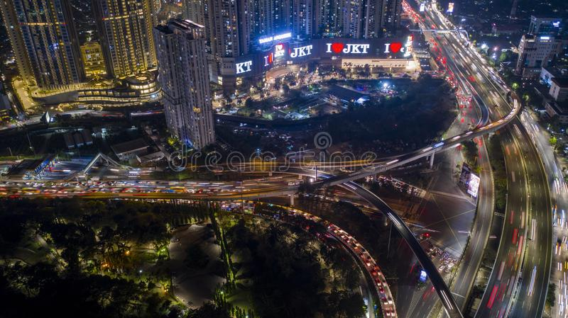 Hectic traffic with skyscrapers at night. JAKARTA - Indonesia. October 22, 2018: Aerial view of hectic traffic on the road interchange with skyscrapers at night royalty free stock photography
