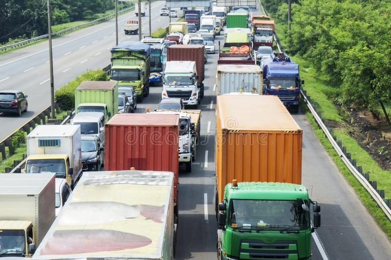 Hectic traffic in a tollway with long row of trucks. Aerial view of hectic traffic in a tollway with long row of trucks in Jakarta, Indonesia royalty free stock photography