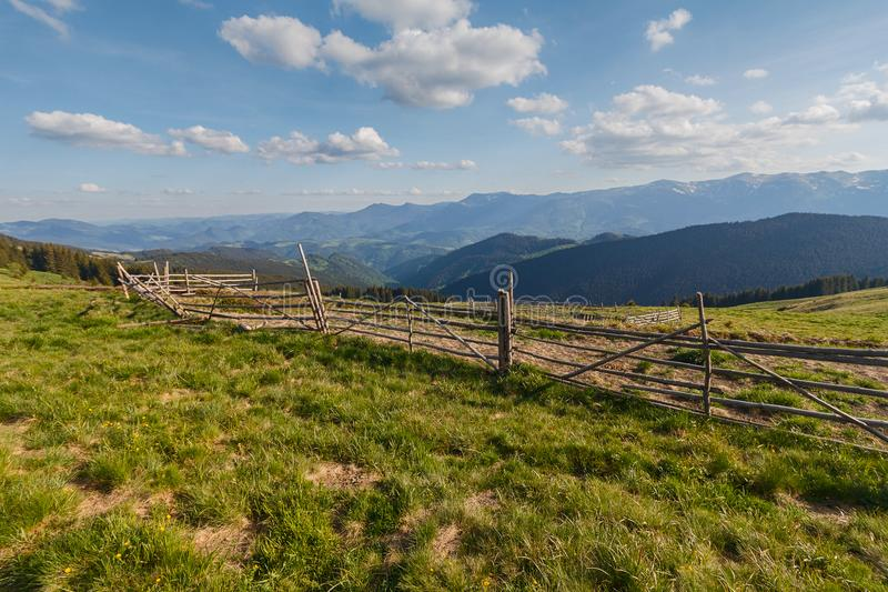 Hedge of pasture against a background of sunlit mountains. Carpathians stock photo