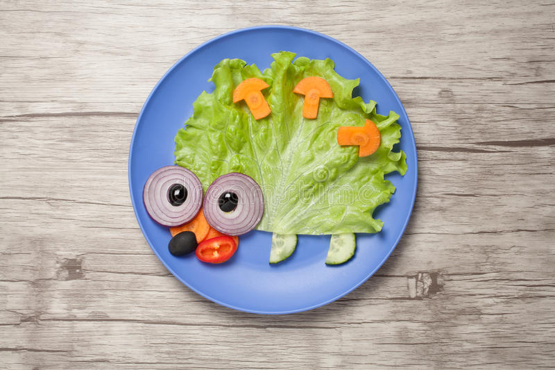 Hedgehog made of vegetables on plate and desk royalty free stock photos