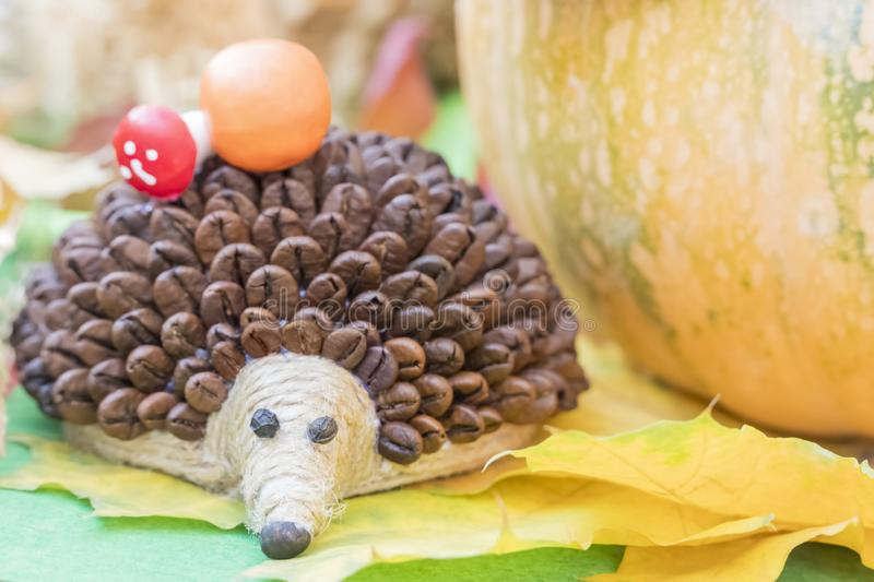 Hedgehog with needles from coffee beans. Children handicraft - hedgehog with needles from coffee beans on yellow autumn leaves royalty free stock photo