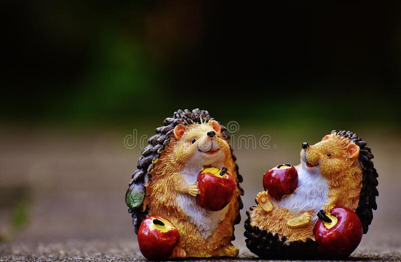Hedgehogs with apples figurines royalty free stock image
