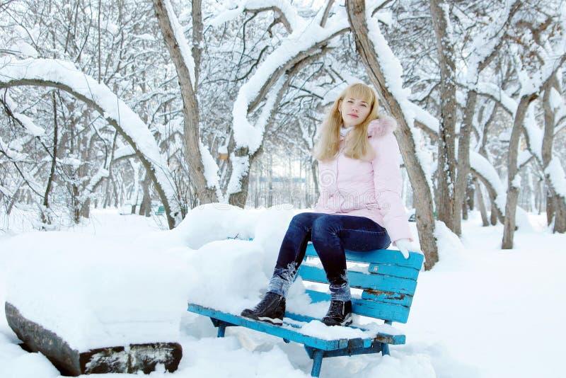 Heeft de blonde jonge mooie vrouw een rust op de bank in een park royalty-vrije stock fotografie