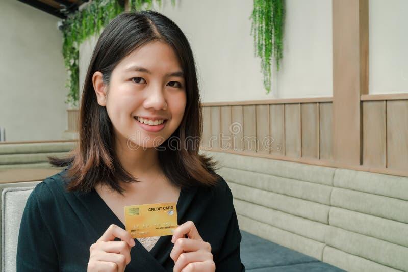 Heeft de close-up Aziatische mooie vrouw die een zwarte overhemdszitting in het huis dragen een creditcard in hand Gelukkig gezic stock foto