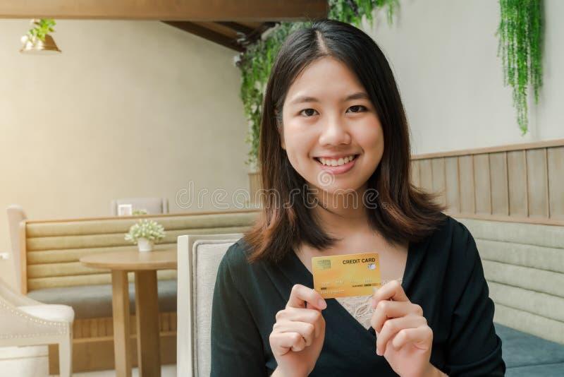 Heeft de close-up Aziatische mooie vrouw die een zwarte overhemdszitting in het huis dragen een creditcard in hand Gelukkig gezic royalty-vrije stock foto