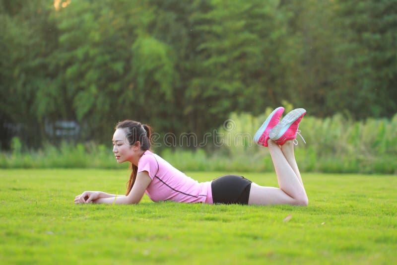 Heeft de geschiktheids Aziatische Chinese vrouw een rust bij gras in een park royalty-vrije stock afbeelding