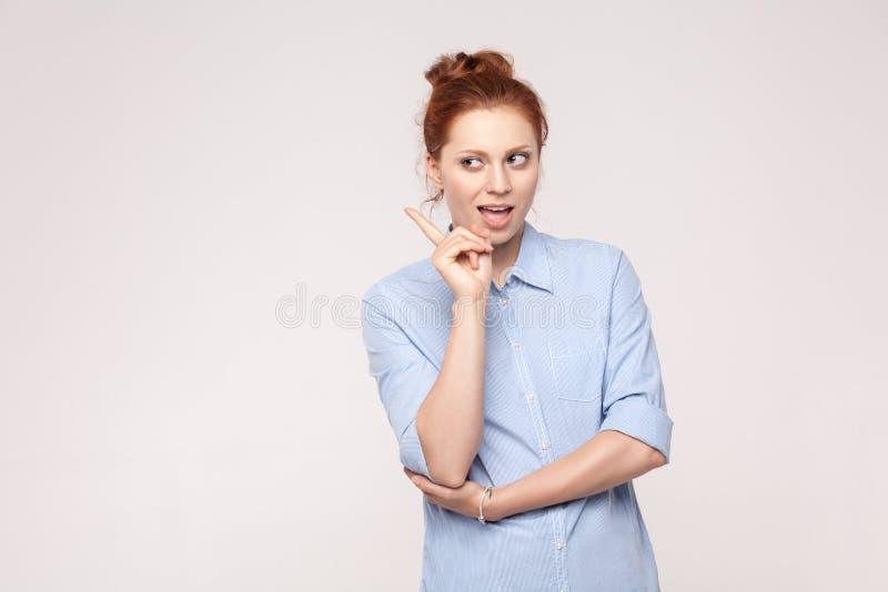 Heeft de Meannes rode haired vrouw een idee of een slecht plan Het kijken weg a stock fotografie