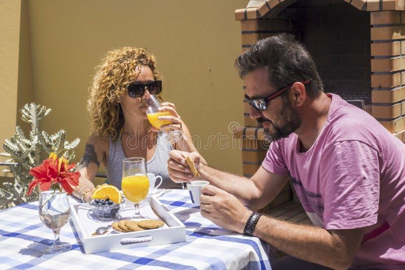 Heeft het jonge Kaukasische paar van Nice samen ontbijt in de tuin thuis onder de zon mooie dag van de zomer of de lente met royalty-vrije stock foto