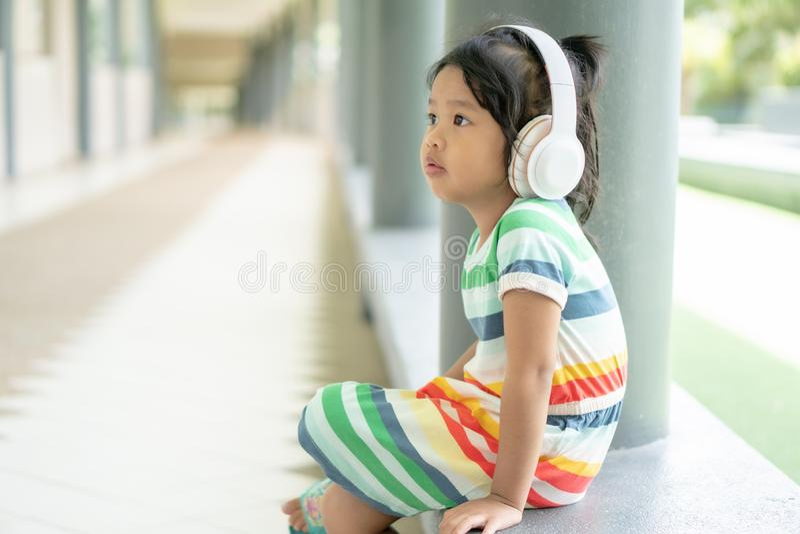 Heel aardig meisje en muziek beluisteren met een koptelefoon... en rustig zitten royalty-vrije stock afbeelding