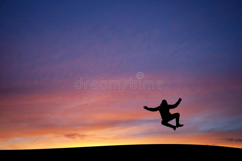 Heel clicking man in sunset. Heel click jump of silhouetted man in sunset stock photos