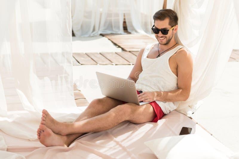Heel jeugdige kerel met baard die gadget gebruiken tijdens de zomervakantie stock afbeelding