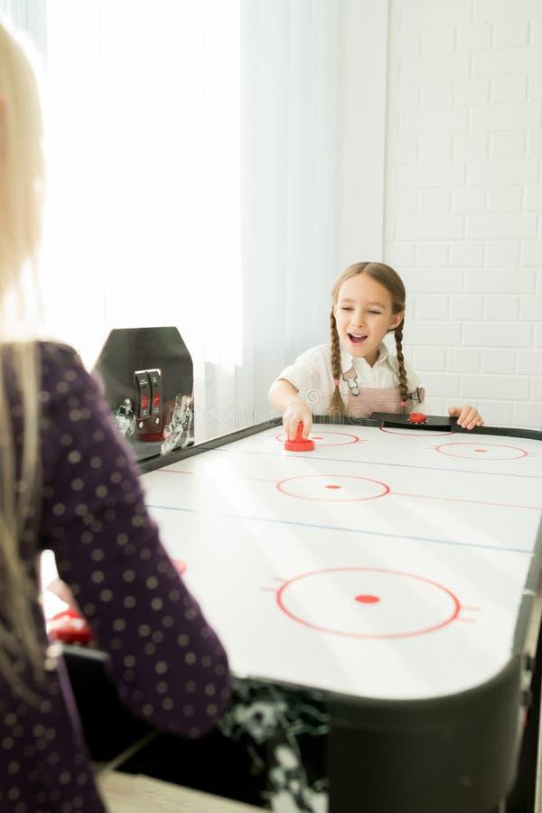 Heel meisje die de striker van het luchthockey met behulp van stock foto