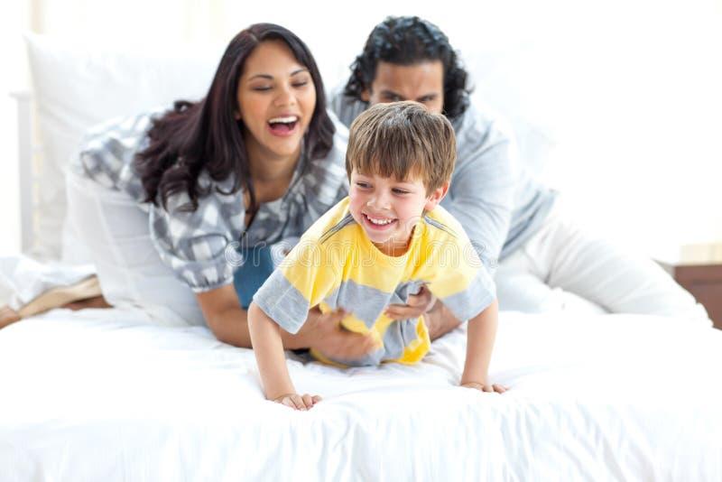 Heel ouders die met hun kleine jongen spelen stock fotografie