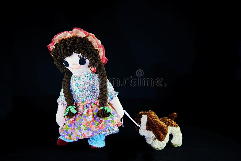 Heel Puppy 2, let`s go for a walk. New pose. Vintage girl rag doll with her puppy; presented on a plain black background. Walking the puppy. Good Puppy Heel royalty free stock images