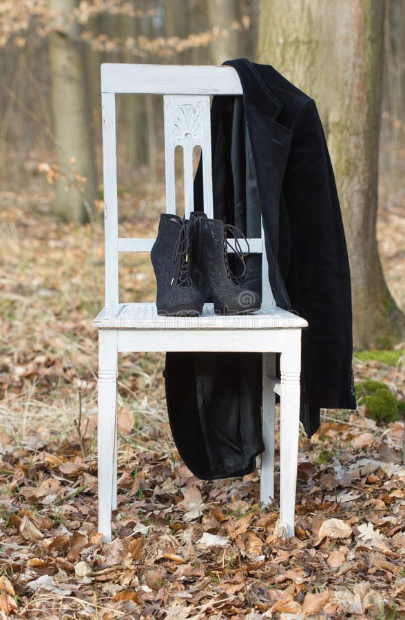 Heel shoes and jacket. A white chair with black heel shoes and jacket in the forest stock photos