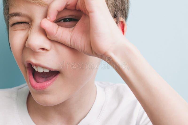 Heel toont de jongen sluiting van zijn glazen met zijn vingers royalty-vrije stock fotografie