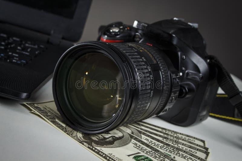 Heel wat dollars dichtbij de camera en laptop stock fotografie