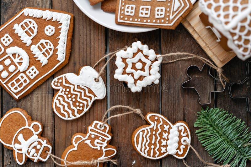 Heel wat gemberkoekjes in verschillende vorm op bruine houten lijst Verfraaid met witte zoete glans De stemming van Kerstmis stock fotografie