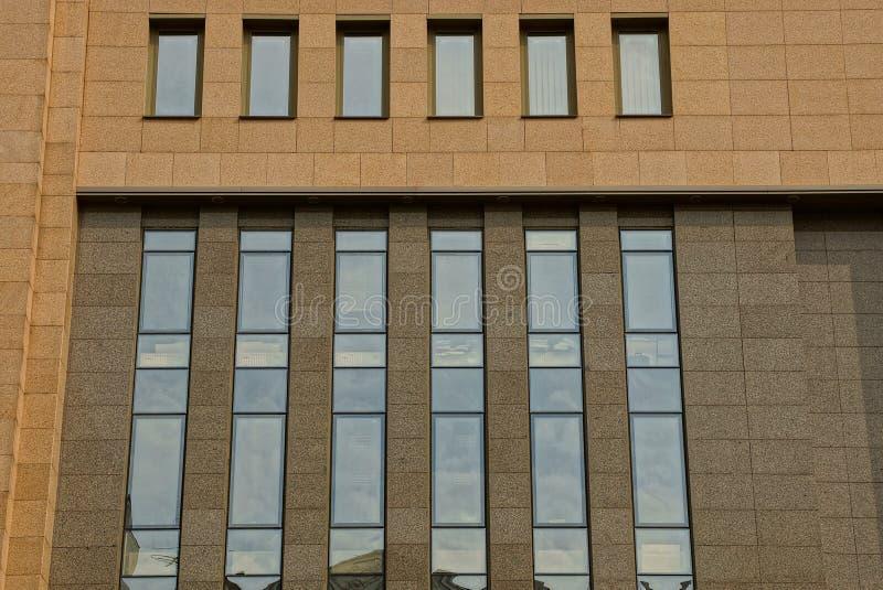 Heel wat glasvensters op de voorgevel van een bruin high-rise gebouw royalty-vrije stock fotografie