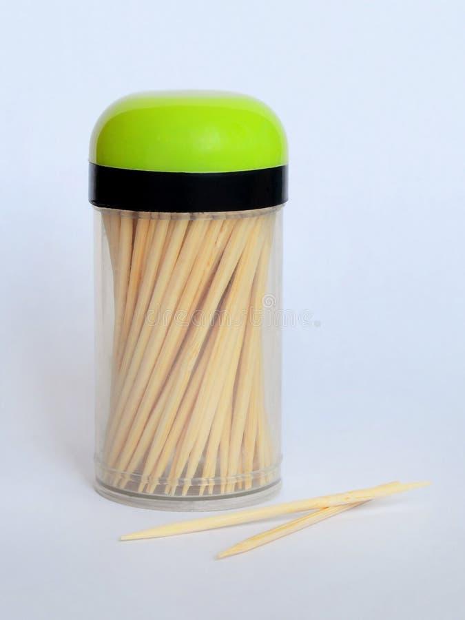 Heel wat houten tandenstokers in een transparante plastic kruik met een zwart en groen deksel op een neutrale achtergrond, close- royalty-vrije stock foto's