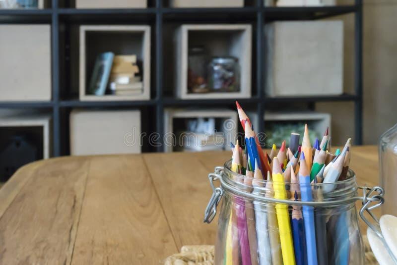 Heel wat kleurenpotloden in de glaskruik zetten op de houten lijst stock afbeelding