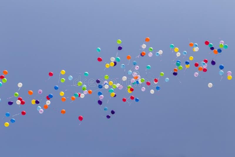 Heel wat kleurrijke ballons die in duidelijke blauwe hemel wegvliegen stock afbeeldingen