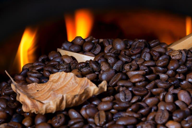 Heel wat koffiebonen met een houten lepel en een droge blad en een vuurgloed royalty-vrije stock afbeeldingen